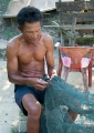 A Seletar sea gypsy mending his fishing ...