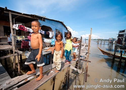 Bajau children walk precariously on rick...