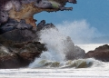 Waves crash against sandstone boulders a...